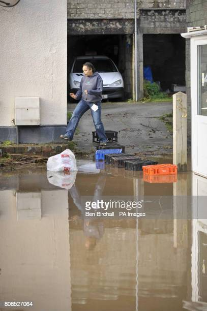 A girl uses milk crates to cross the driveway of a house is affected by floodwater in St Blazey Cornwall where flooding has closed the village off...