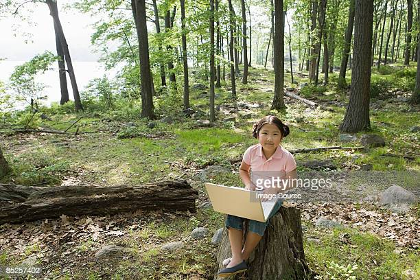 A girl using a laptop in a forest
