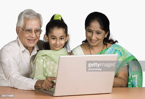 Girl using a laptop with her grandparents and smiling