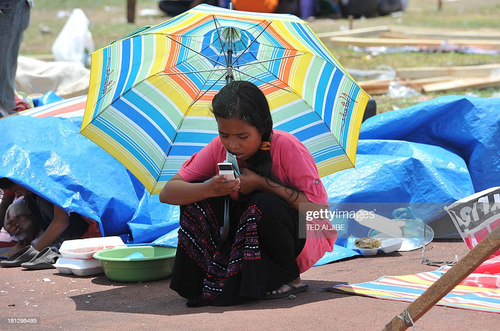 A girl using an umbrella to shelter from the scorching heat browses her mobile phone as she queues up for food distribution at an evacuation centre inside a sports complex in Zamboanga on the southern Philippine island of Mindanao on September 20, 2013. Philippine security forces killed eight Muslim rebels on September 20 as they hunted the remnants of a guerrilla force hiding in homes of the major city and believed to be holding hostages.