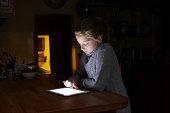 Girl using digital tablet in kitchen at night