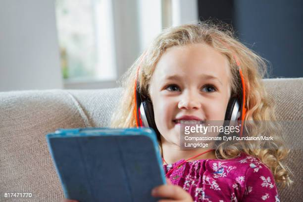 Girl using digital tablet with headphones on sofa