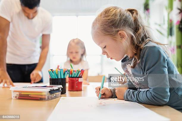 Girl using felt tip pen in drawing class with classmate and teacher in background
