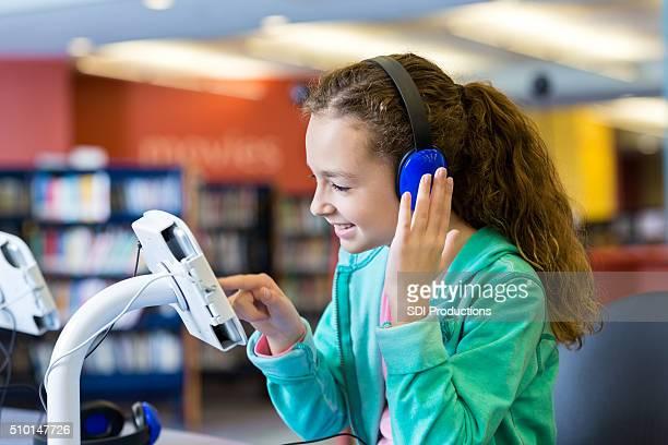 Casque et fille à l'aide d'une tablette pour écouter bibliothèque livre audio