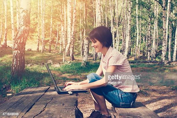 Girl using lap top among nature