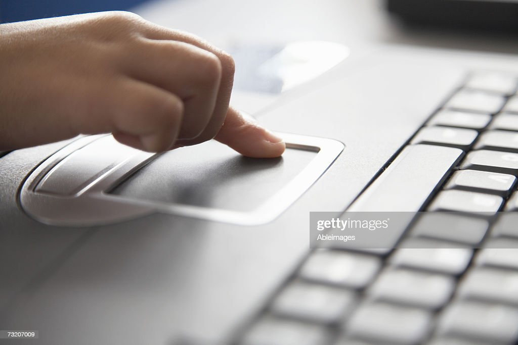 Girl (5-7) using laptop, close-up of finger on touchpad : Stock Photo
