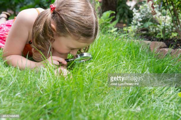 Girl using magnifying glass in grass