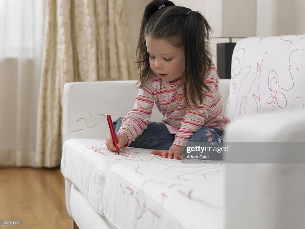 Girl using marker on sofa : Stock Photo