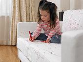Girl using marker on sofa