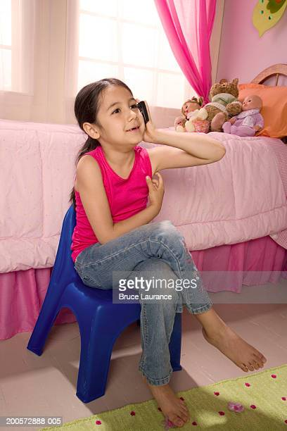 Girl (6-7) using mobile phone in bedroom