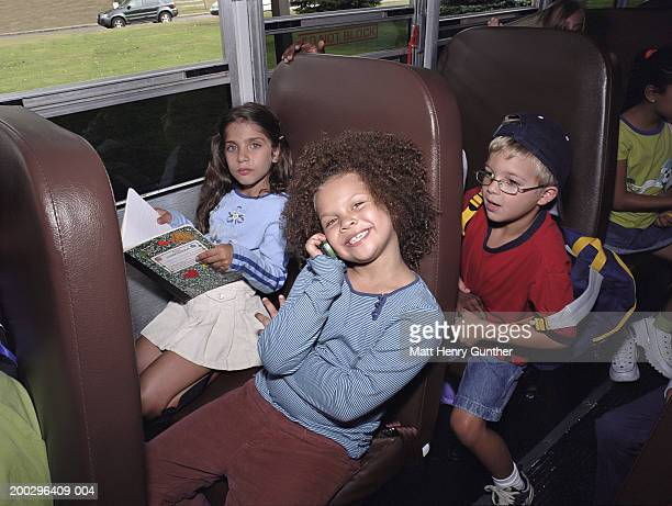 Girl (6-8) using mobile phone on schoolbus, smiling, portrait