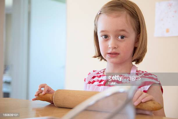 Girl using rolling pin in kitchen