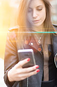 Portrait of a girl using her smart phone, sunset light is coming from behind her.