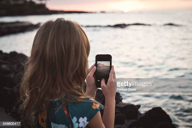 Girl Using SmartPhone to take picture of sunset