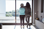 Girl visiting grandma. Back view of young and elderly women standing and looking out window. Family and taking care concept