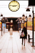 Girl waiting for train on platform. Clock close up.