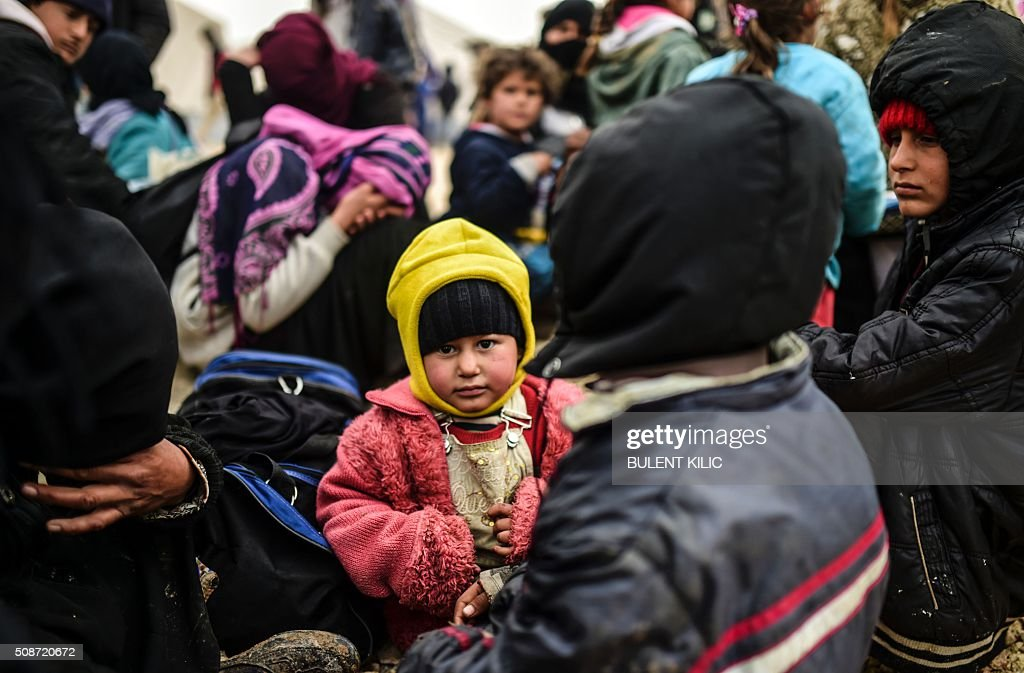 A girl waits as Syrians fleeing the northern embattled city of Aleppo wait on February 6, 2016 in Bab al-Salam, near the city of Azaz, northern Syria, near the Turkish border crossing. Thousands of Syrians were braving cold and rain at the Turkish border Saturday after fleeing a Russian-backed regime offensive on Aleppo that threatens a fresh humanitarian disaster in the country's second city. Around 40,000 civilians have fled their homes over the regime offensive, according to the Syrian Observatory for Human Rights monitor. / AFP / BULENT KILIC