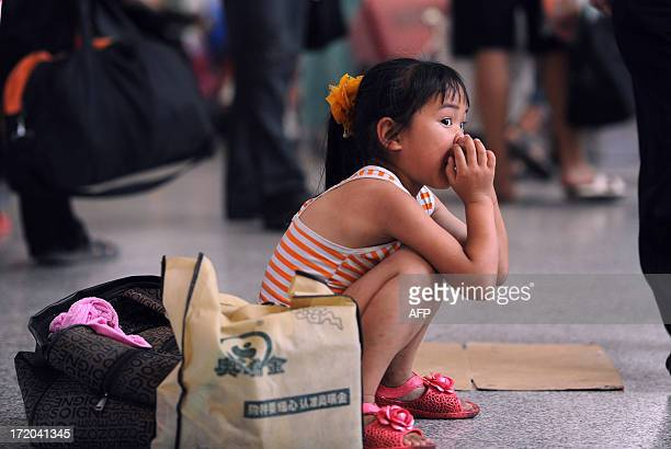 A girl waits for the train at Hefei railway station in Hefei north China's Anhui province on July 1 2013 China's summer travel peak starts on July 1...