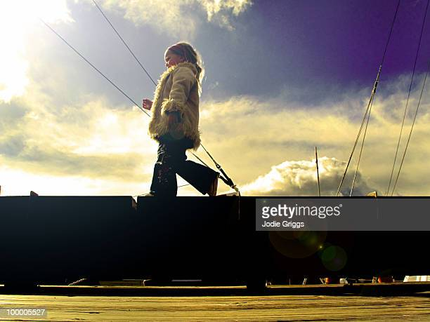 Girl walking along boardwalk at wharf