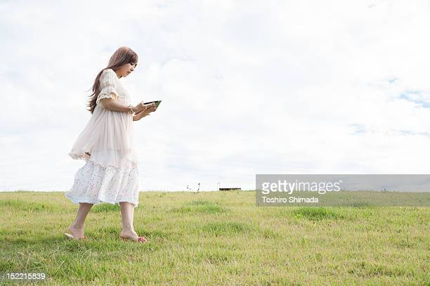 Girl walking and using tablet pc