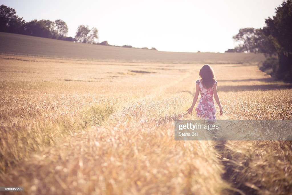 Girl walking In barley field : Stock Photo