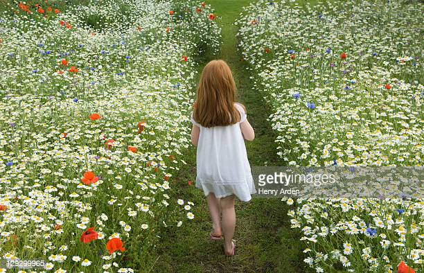 Mädchen zu Fuß in Feld mit Blumen