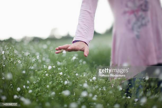 Girl walking in field of flowers