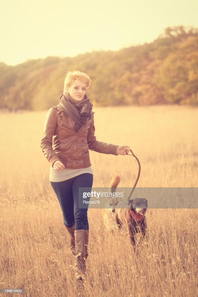 girl walking in the autumn meadow with her dog : Stock Photo