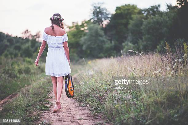 Girl walking in the guitar in nature