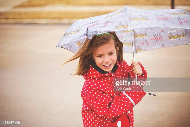 Girl walking in the rain with umbrella