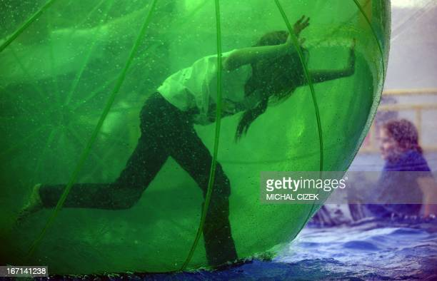 A girl walking inside a giant plastic ball rolls it over the water at Prague's traditional amusement park at Holesovice fairground during a sunny day...