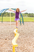 Front view of a young girl walking across a yellow balance beam in the park playground. Taken on a cloudy summer day. There is also a splash pad at this park, so the girl is wearing a purple rashguard