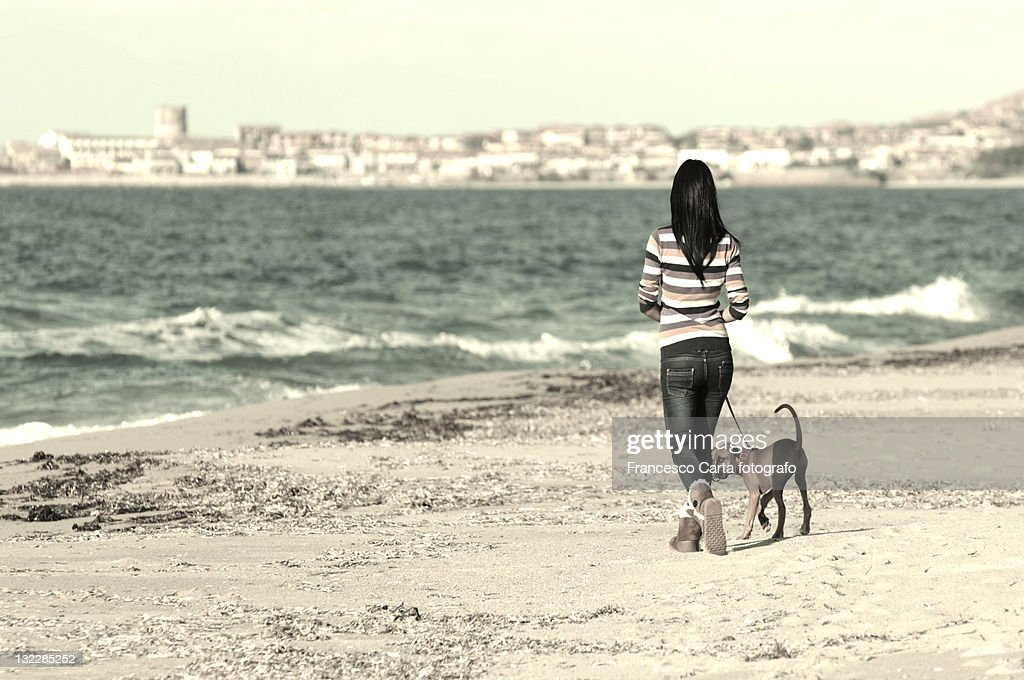 Girl walking on beach with dog : Stock Photo