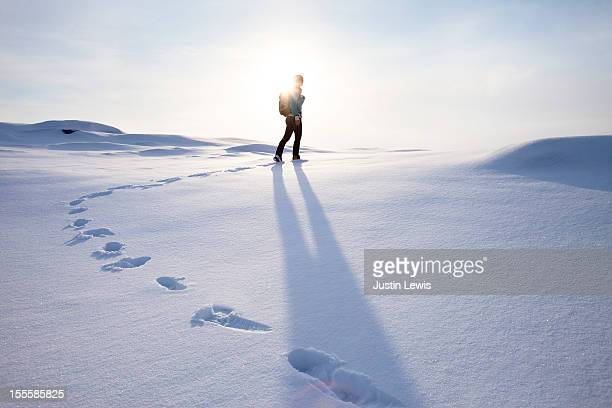 Girl walking on fresh snow with foot steps and sun
