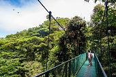 Girl walking on hanging bridge in cloudforest - Monteverde, Costa Rica - adventure in central america
