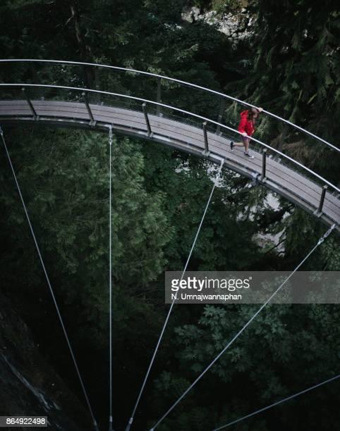 A girl walking on the bridge in Capilano park