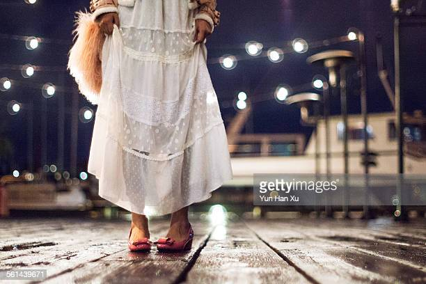 Girl walking on the dock in the rain at night