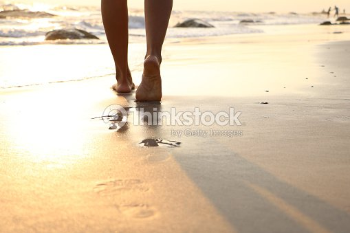 Girl walking on wet sandy beach leaving footprints