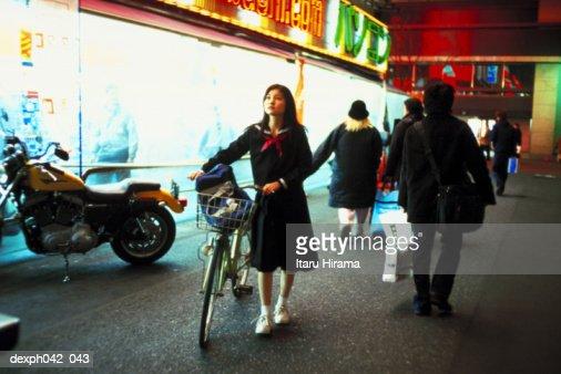 Girl walking, pushing a bicycle