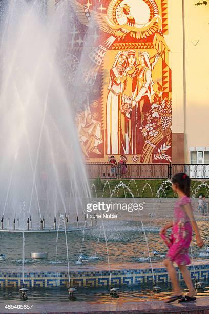 Girl walking round fountain near Amir Temur Park
