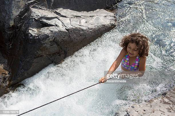 A girl walking up stream in a creek using a rope
