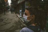 Girl walking wearing a mask in the city street.