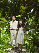 Girl walking with grandfather through jungle