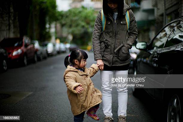 girl walking with mom in a raining day