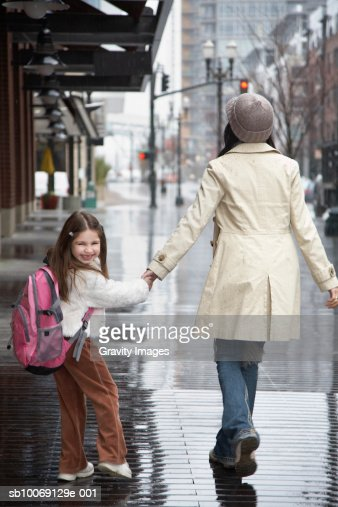 Girl (8-9) walking with mother on street : Stock Photo