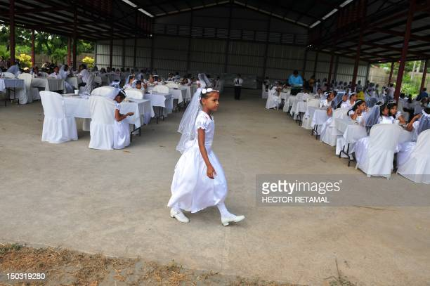A girl walks after a mass in which about 150 children received their first communion at the Metropolitan cathedral in Managua on August 15 2012 AFP...