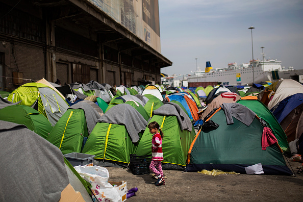A girl walks among tents outside a passenger terminal used as a shelter for refugees and migrants at the Piraeus harbour in Athens on April 3, 2016. Greek and EU authorities were putting the final ...