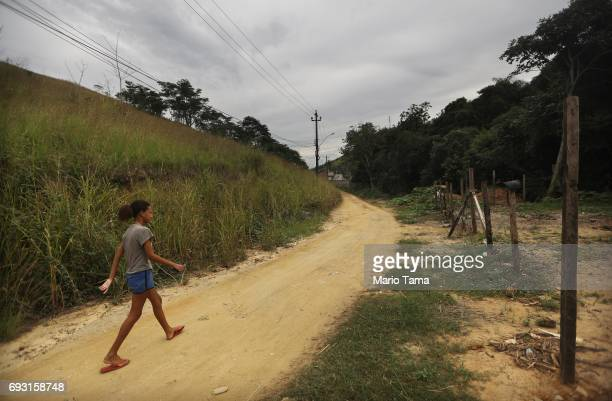 A girl walks down a road in a suburb which is a deforested section of the Atlantic Forest on June 6 2017 in Queimados Rio de Janeiro Brazil The...