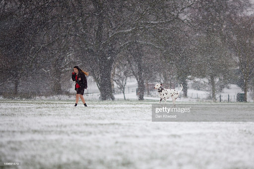A girl walks her dog through Brockwell Park on January 18, 2013 in London, England. Widespread snowfall is affecting most of the UK with school closures and transport disruption. The Met Office has issued a red weather warning for parts of Wales, advising against all non-essential travel as up to 30cm of snow is expected to fall in some areas today.