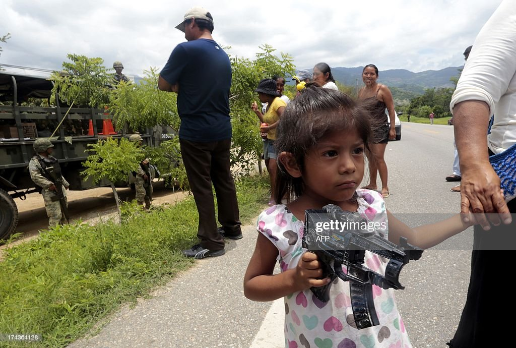 A girl walks holding a toy gun as residents stop a group of soldiers to prevent them from disarming the community police on July 24, 2013 in the village of Xaltianguis, a rural zone in the southwestern State of Guerrero, Mexico. Since last December, hundreds of civilians armed with rifles, pistols and machetes created a vigilante force, stating that gangs were committing robberies, kidnappings and murders. Guerrero, home to the Pacific resort town of Acapulco, has been one of the hardest hit by Mexico's drug violence, which has left more than 70,000 people killed across the country since 2006. AFP PHOTO/Pedro Pardo